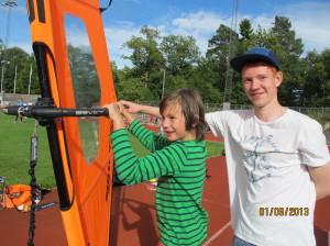 Emil Aslaksrud viser et besøkende barn hvordan seile brett - Idrettens dag 1. sep 2013